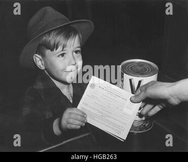 An eager school boy gets his first experience in using War Ration Book Two. circa 1943 - Stock Photo