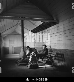 Passengers waiting at a railroad station for next train back to Chicago, 1943. - Stock Photo
