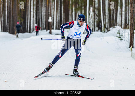 male skier athlete men in winter woods free style during Championship on cross country skiing - Stock Photo
