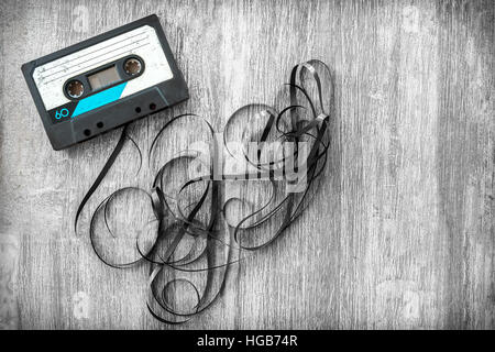 audio tape rolled out background wood vintage unroll compact cassette playlist musicassette - Stock Photo