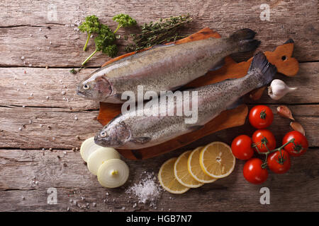 raw rainbow trout with ingredients on a wooden table. Horizontal top view - Stock Photo