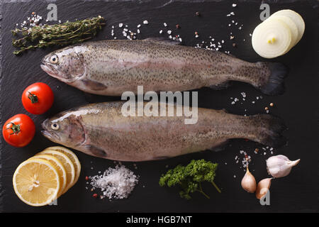 Two raw rainbow trout with ingredients on a slate board closeup. horizontal view from above - Stock Photo