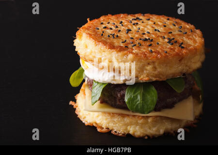 New ramen burger with beef and eggs close-up on a black background. horizontal - Stock Photo