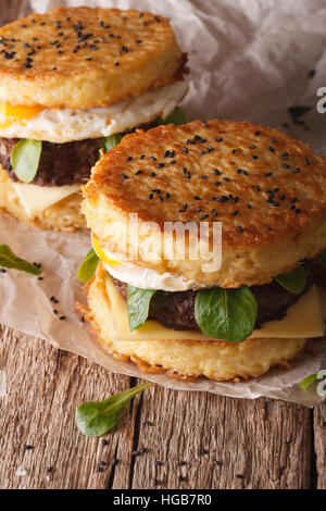 New fast food: ramen burger close-up on a paper on the wooden table. Vertical - Stock Photo