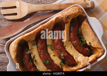 English food: toad in the hole into a baking dish close up on the table. Horizontal top view - Stock Photo
