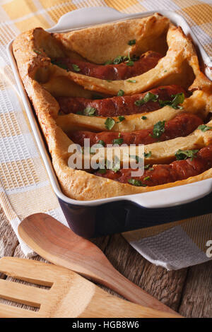 English food: delicious sausages into a baking dish close up on the table. vertical - Stock Photo