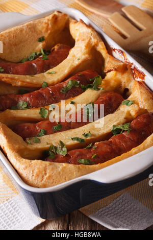 toad in the hole in baking dish close up on the table. Vertical - Stock Photo