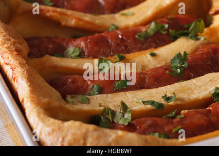 English sausage baked in pastry in a dish macro. horizontal - Stock Photo