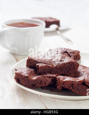 brownies  on a plate, a cup of coffee on the white wooden background - Stock Photo