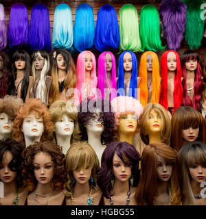Vividly colorful wigs on mannequin heads inside a shop in the Fashion District, Los Angeles, California. - Stock Photo