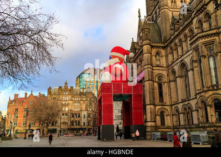 Historic Manchester Town Hall in Albert Square decorated for festive season with a large figure of Father Christmas. - Stock Photo