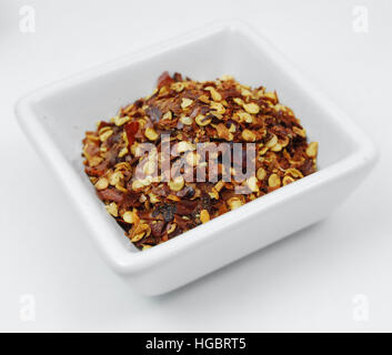 Red pepper flakes in a little spice bowl on a white background - Stock Photo