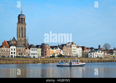 DEVENTER, THE NETHERLANDS - DECEMBER 24, 2016: Ferry is crossing the river IJssel with a view of the medieval city - Stock Photo