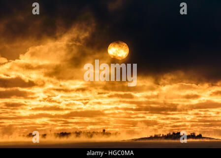 Setting sun shining through dark winter clouds above freezing Baltic Sea in Helsinki, Finland with sea fog raising - Stock Photo