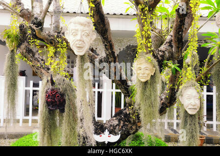 Sculpted stone heads hanging from a tree at wat rong khun, white temple in chiang rai northern thailand. - Stock Photo