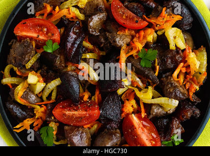 Pieces of roast duck, goose (meat, liver, heart) with vegetables (onion, carrot, tomato) on a round cast-iron frying - Stock Photo
