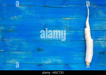 One root of daikon radish on a blue (sapphire) wooden background. The top view. Space for your text. - Stock Photo