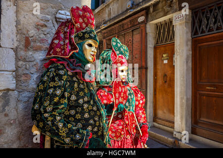 Couple of participants in colorful dresses and masks on old street of Venice during traditional famous Carnival. - Stock Photo