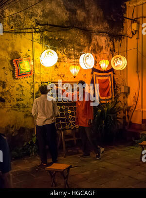 Two men playing a large size chinese chess game at night, in the streets of Hoi An, Vietnam. - Stock Photo