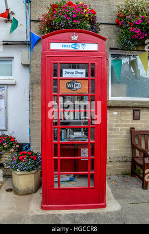 Old red telephone box now used as a book swap with public Wi-Fi available in Beer Devon West Country UK - Stock Photo