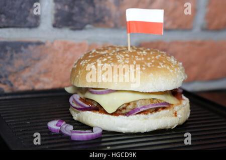 Hamburger with beef, cheese, onion, tomato and sauce. Homemade burger. Polish flag - Stock Photo