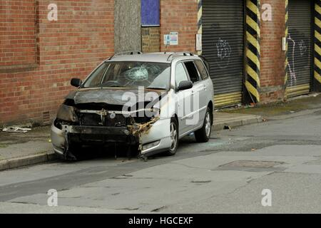 Burned out car with smashed windscreen by the side of the road in an industrial area of a city - Stock Photo