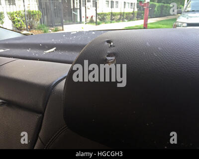 Bullets pass through the head rest of a car parked in front of a senior citizen home during a drive by shooting - Stock Photo