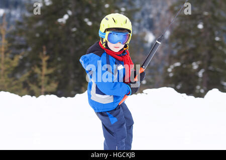 Young child, going up a hill with a surface lift, standing on the ground, using button ski lift. Little skier, learning - Stock Photo