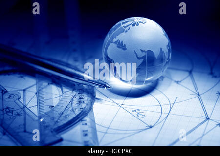 Business concept. Glass globe near rulers on graph paper surface with draft - Stock Photo