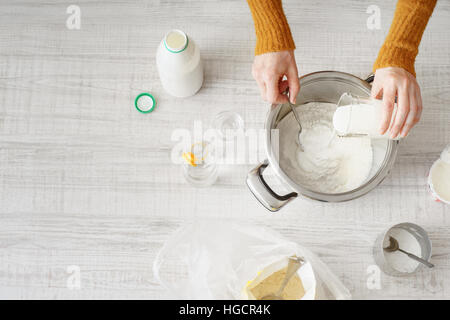 Woman makes the dough in the pan horizontal - Stock Photo