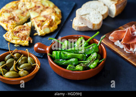 Authentic Spanish tapas with padron peppers,  caperberries and traditional tortilla - Stock Photo