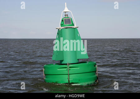 A green channel marker buoy in the water. - Stock Photo