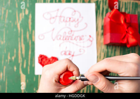 Man writing a Valentines day card and preparing a present - Stock Photo