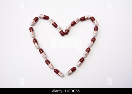 Red and white pill capsules with 'venus' gender symbol representing female, or woman, against a white background. - Stock Photo