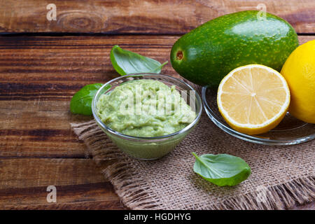 avocado guacamole sauce with ingredients, traditional Mexican dip and ingredients - Stock Photo