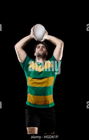 Rugby player in a green and gold uniform. Black Background - Stock Photo