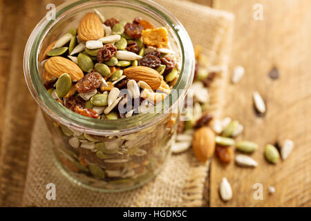Dried fruit and nuts trail mix with almonds, raisins, seeds and apples in a glass jar - Stock Photo