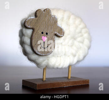 Wool knitted smiling wooden sheep decoration - Stock Photo