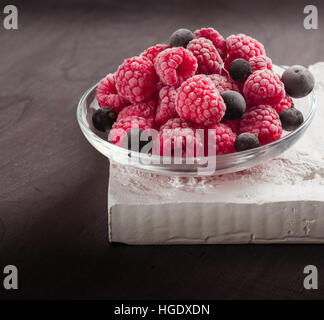 Frozen raspberries in a glass saucer. Frost on the berries. Dark background. - Stock Photo