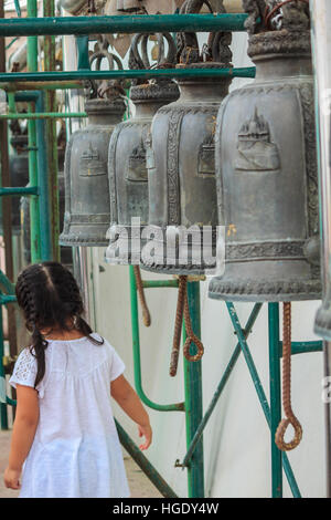 Girl white shirt with row of bells in buddhist temple in Thailand. Buddhist temple bells. Bells of the old temple - Stock Photo