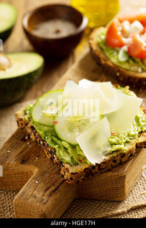 Avocado toast with cucumber and parmesan - Stock Photo