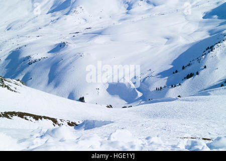 Snowy mountain valley crisscrossed by ski tracks on groomed slopes and off piste - Stock Photo