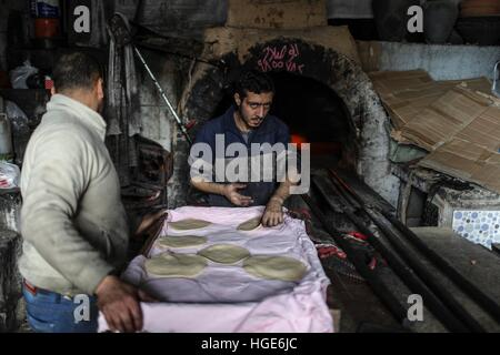 Gaza. 3rd Jan, 2017. A man bakes bread in front of a traditional wood-fired oven at a local bakery in Gaza City, - Stock Photo