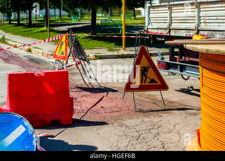 Warning signs for work in progress on road under construction.  fiber optic cables buried in a micro trench with - Stock Photo