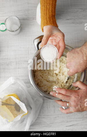 Man and woman makes the dough in the pan on the table vertical - Stock Photo
