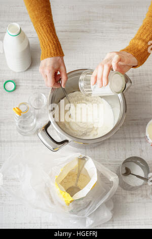 Woman makes the dough in the pan on the white table vertical - Stock Photo