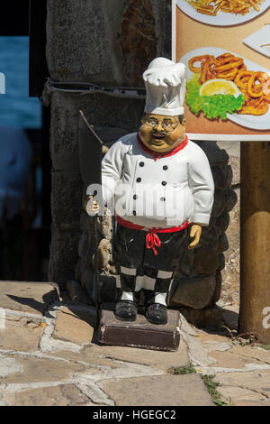 Plaster figure chef in front of restaurant - Stock Photo