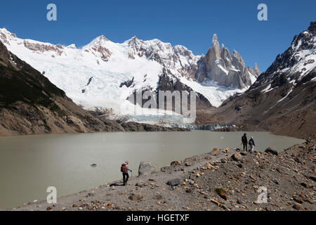Hikers walking by Laguna Torre with view of Cerro Torre, El Chalten, Patagonia, Argentina, South America - Stock Photo