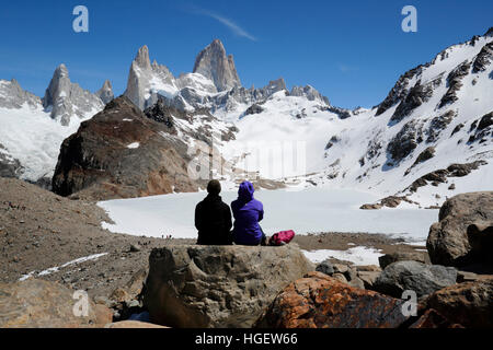 Hikers above Laguna de los Tres with view of Mount Fitz Roy, El Chalten, Patagonia, Argentina, South America - Stock Photo