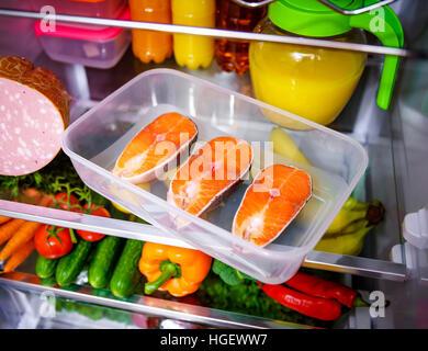 Raw Salmon steak in the open refrigerator - Stock Photo